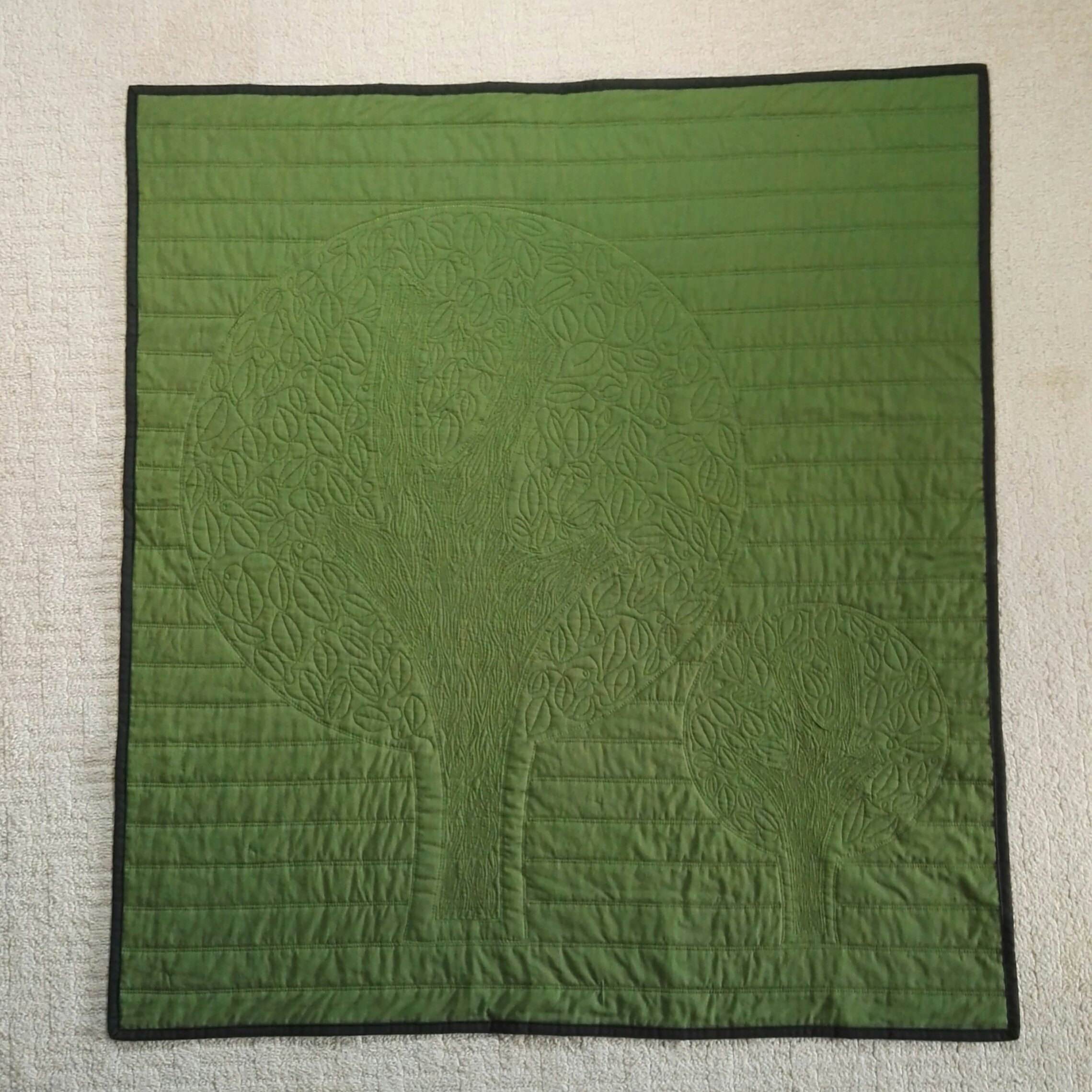 Back of scrappy quilt with tree applique
