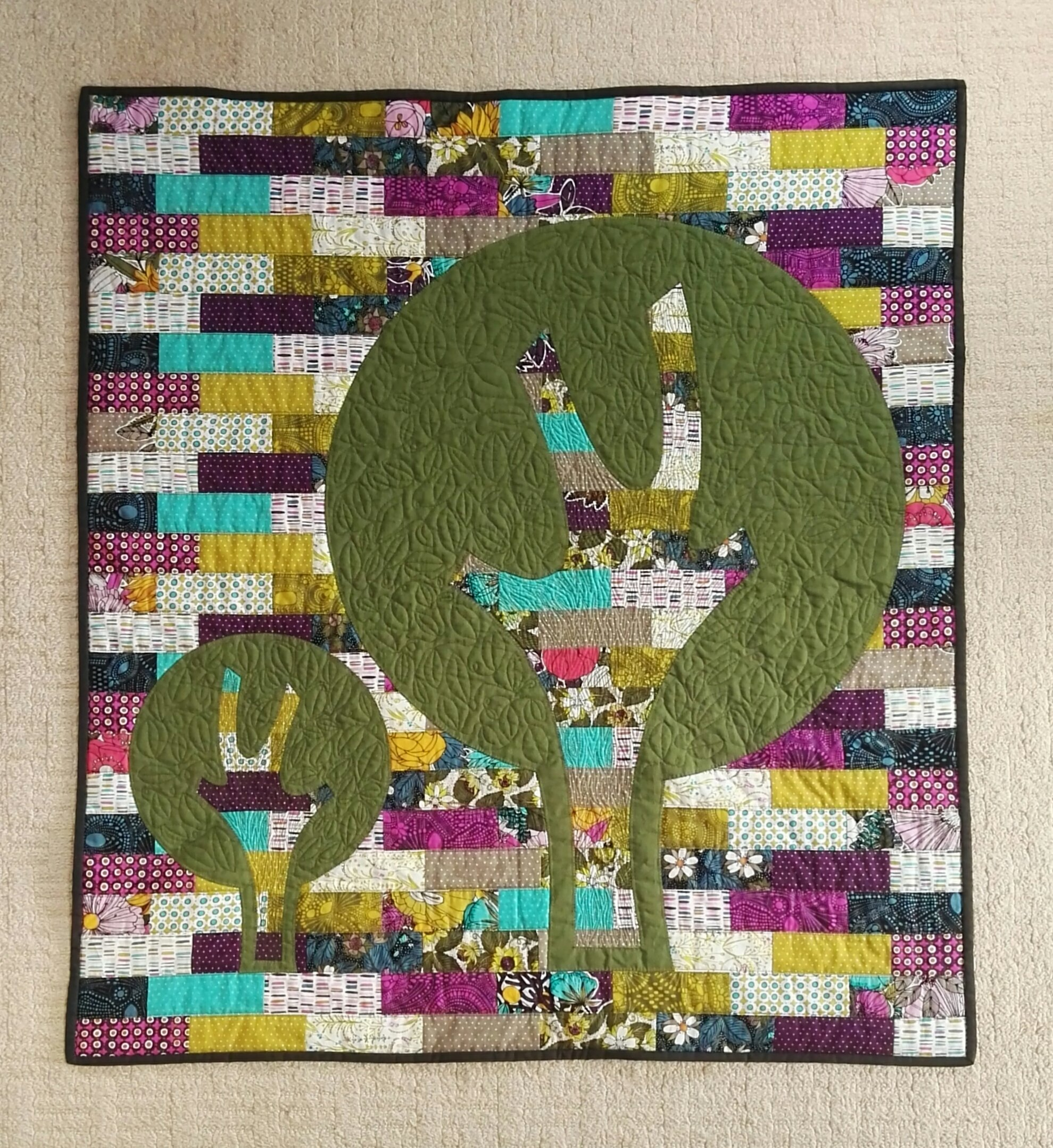 Scrappy quilt with Tree Applique